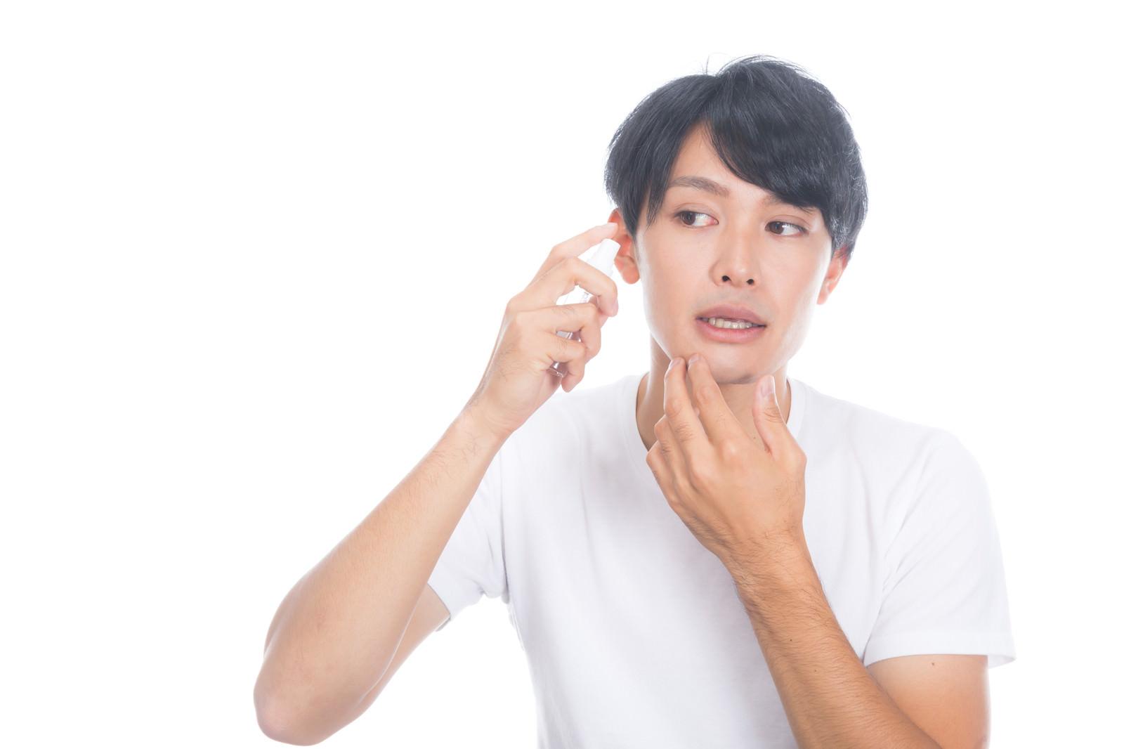 「化粧水を頬に噴射する男性」の写真[モデル:完伍]