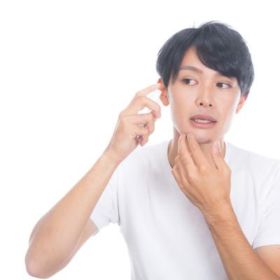 「化粧水を頬に噴射する男性」の写真素材