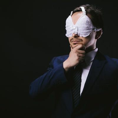 「絶妙なフィット感のアイマスクに満足する会社員」の写真素材