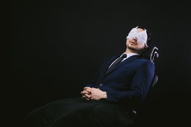 業務中にレースのアイマスクを装着して仮眠を取るサラリーマンの写真