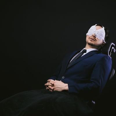 「業務中にレースのアイマスクを装着して仮眠を取るサラリーマン」の写真素材