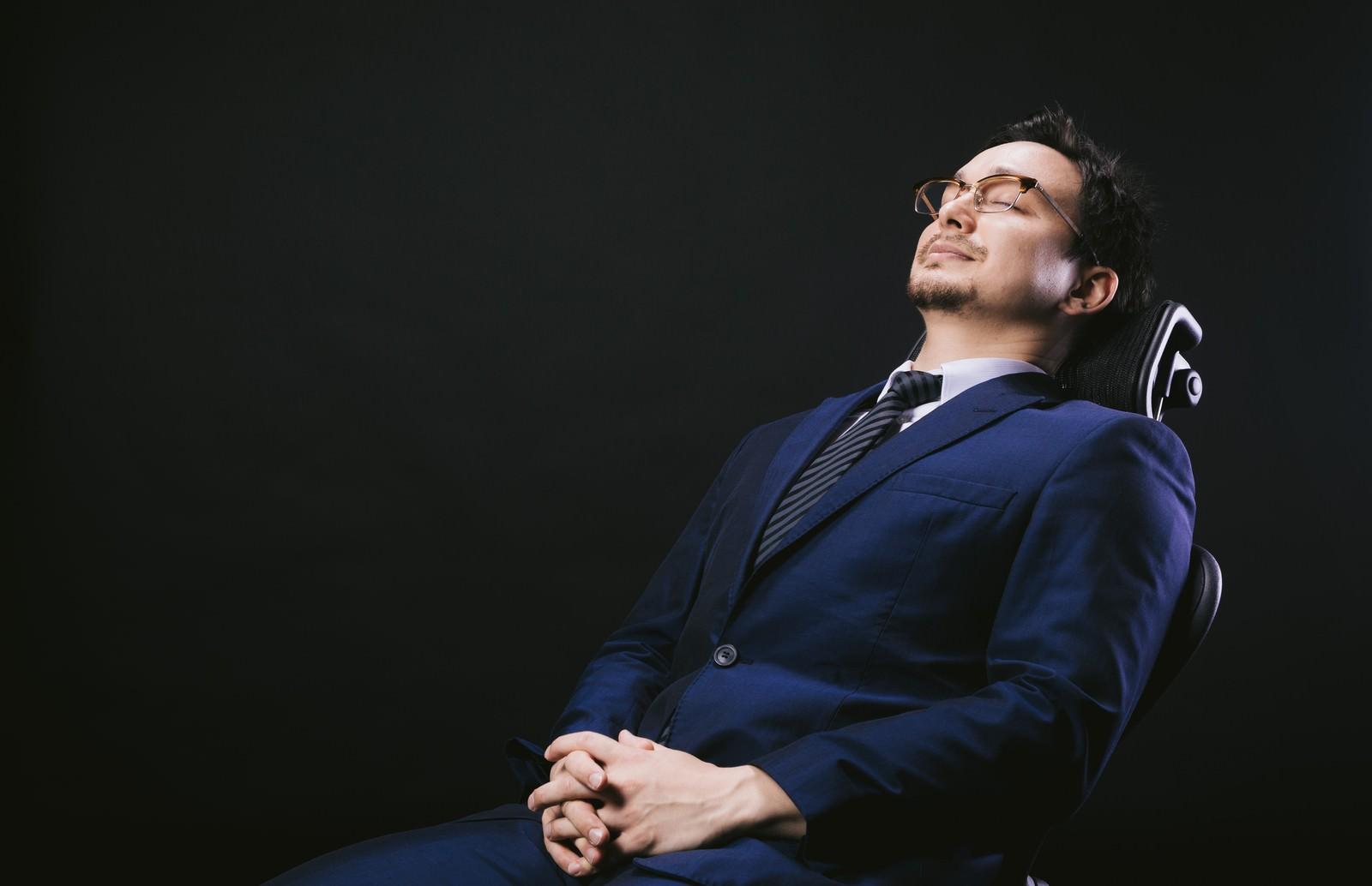 「リクライニングチェアで寝落ちする会社員」の写真[モデル:Max_Ezaki]