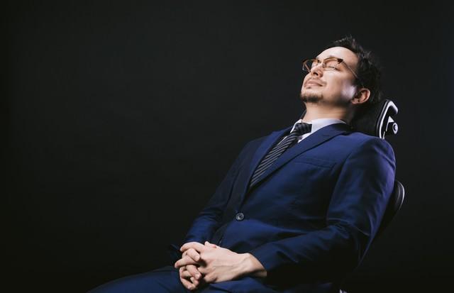 リクライニングチェアで寝落ちする会社員の写真
