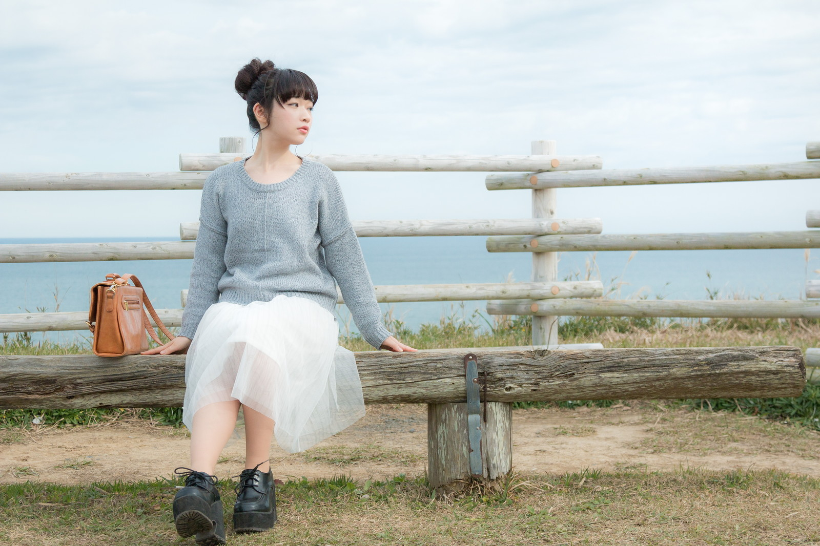 「海が一望できる岬のベンチに座る若い女性」の写真[モデル:渡辺友美子]