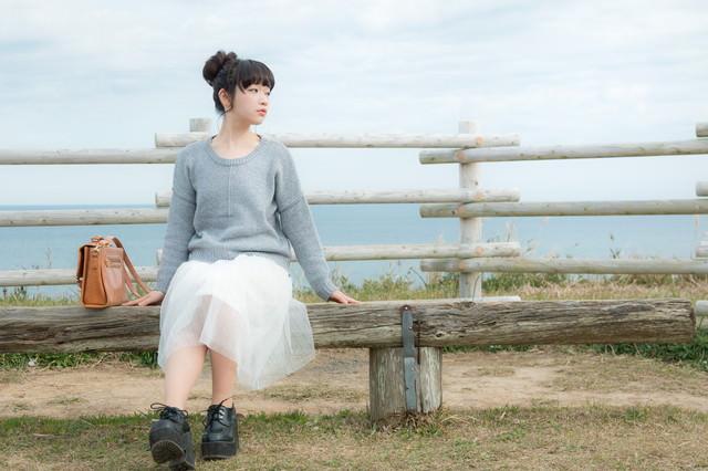海が一望できる岬のベンチに座る若い女性の写真