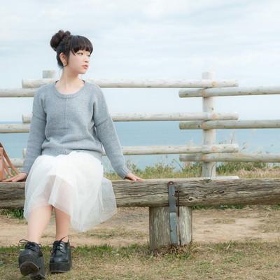 「海が一望できる岬のベンチに座る若い女性」の写真素材