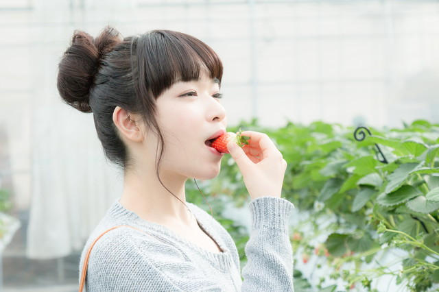 甘いいちごにご満悦の女性の写真