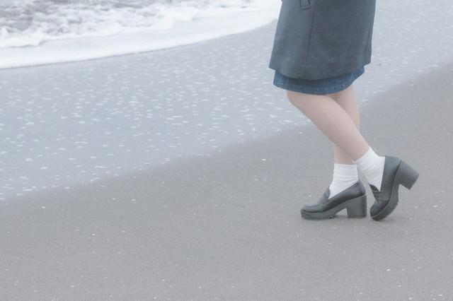 波打ち際でたたずむ女性の足元の写真