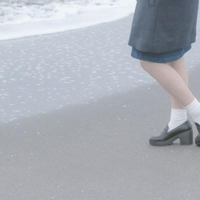 「波打ち際でたたずむ女性の足元」の写真素材
