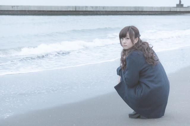 砂浜でいじける女性の写真