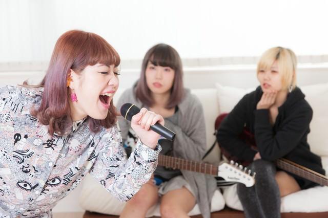 カラオケで熱唱するバンドのボーカルの写真