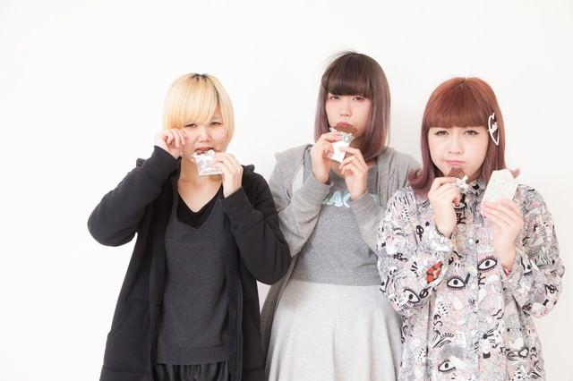 板チョコを噛みしめる女性三人組の写真
