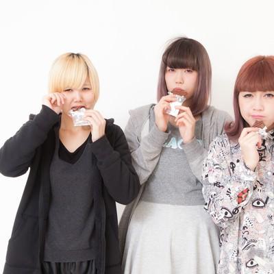 「板チョコを噛みしめる女性三人組」の写真素材