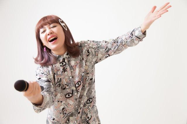 オーディエンスにサビを歌わせる女性ボーカルの写真