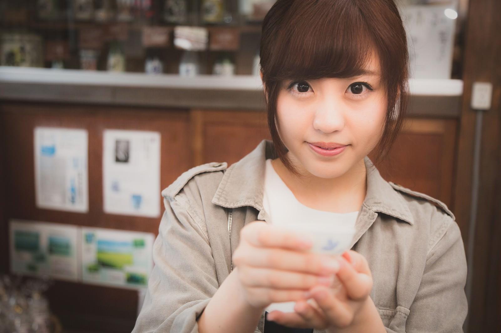 「試飲を勧める日本酒好きの女の子」の写真[モデル:河村友歌]