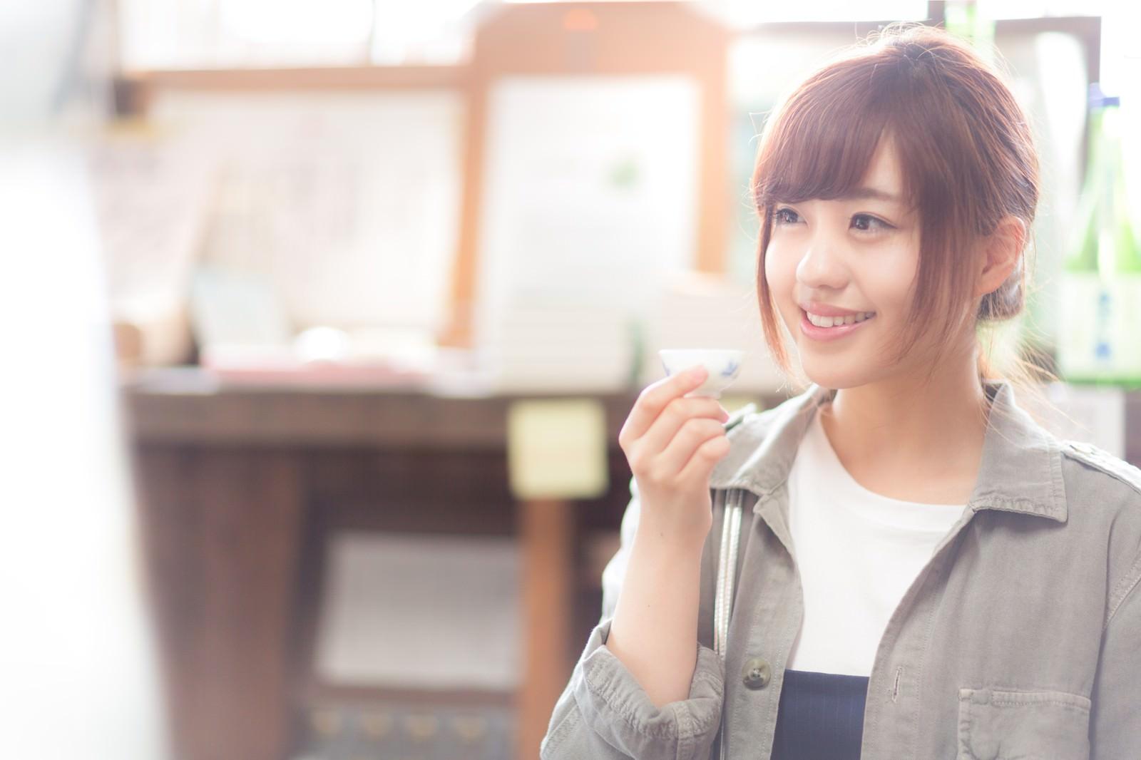 「純米酒を堪能し笑顔がこぼれる女性」の写真[モデル:河村友歌]