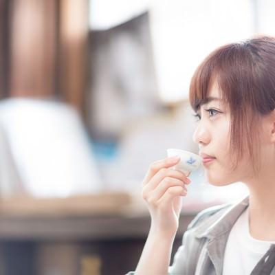蔵元で日本酒をいただく若い女性観光客の写真