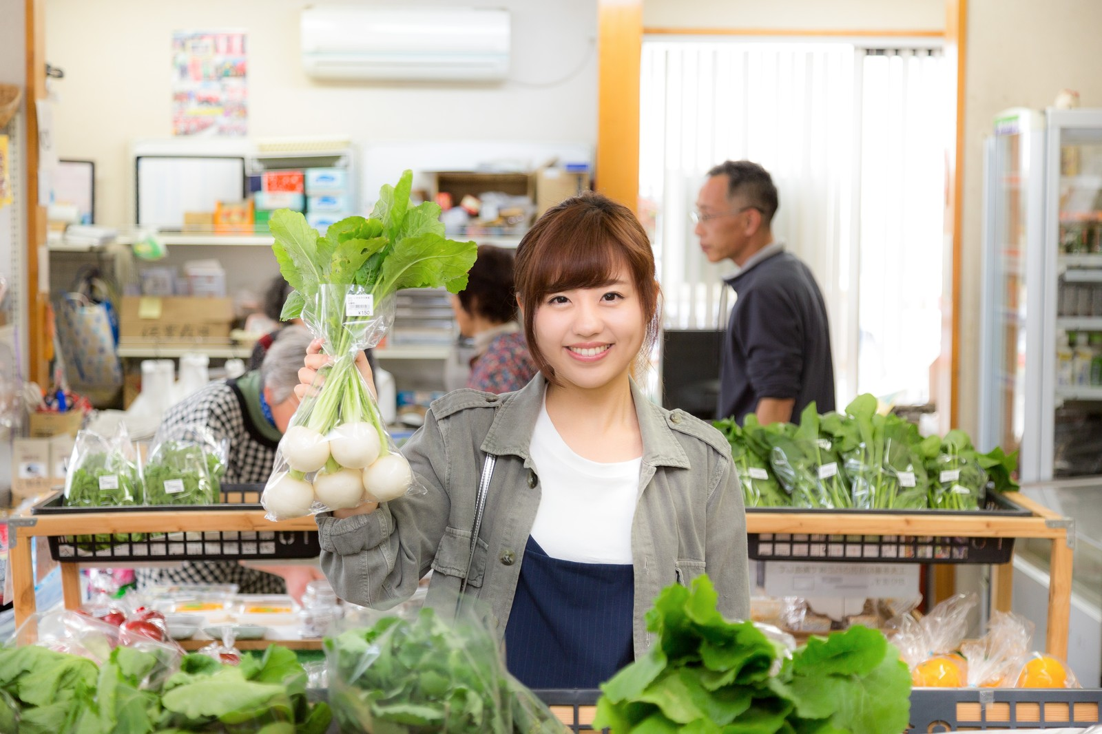 「「株あがれー」の笑顔で店主のお株を奪う女性観光客とふれあい市場の様子」の写真[モデル:河村友歌]