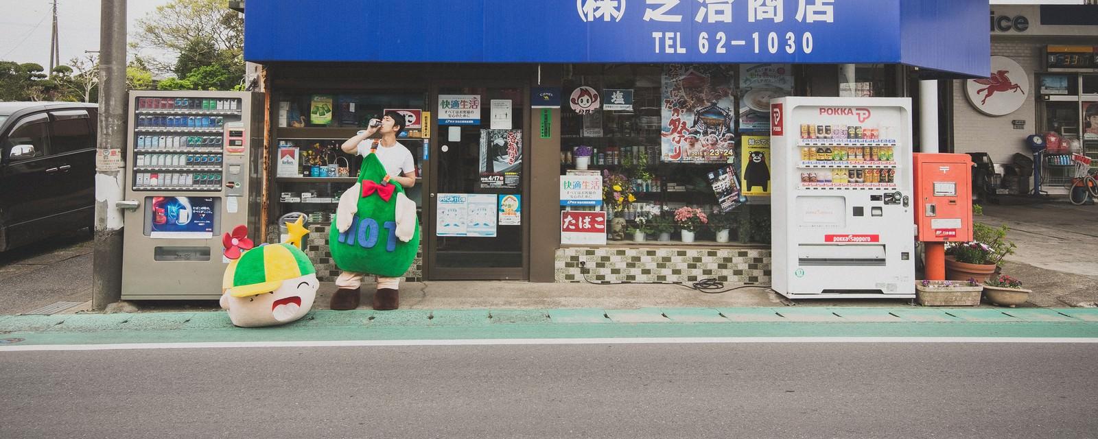 「商店の前でコーヒーを飲むゆるキャラと中の人」の写真[モデル:大川竜弥 ホットくん]