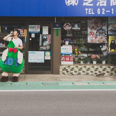 商店の前でコーヒーを飲むゆるキャラと中の人の写真
