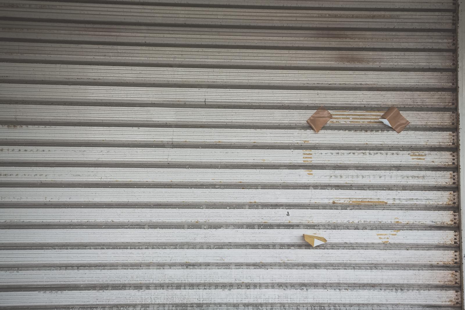 「張り紙の跡が残るシャッター」の写真