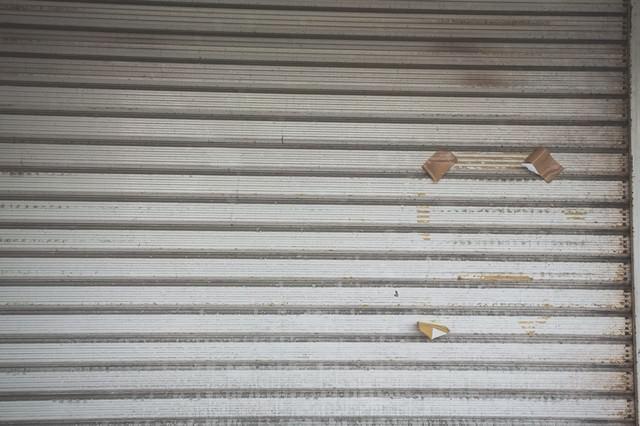 張り紙の跡が残るシャッターの写真