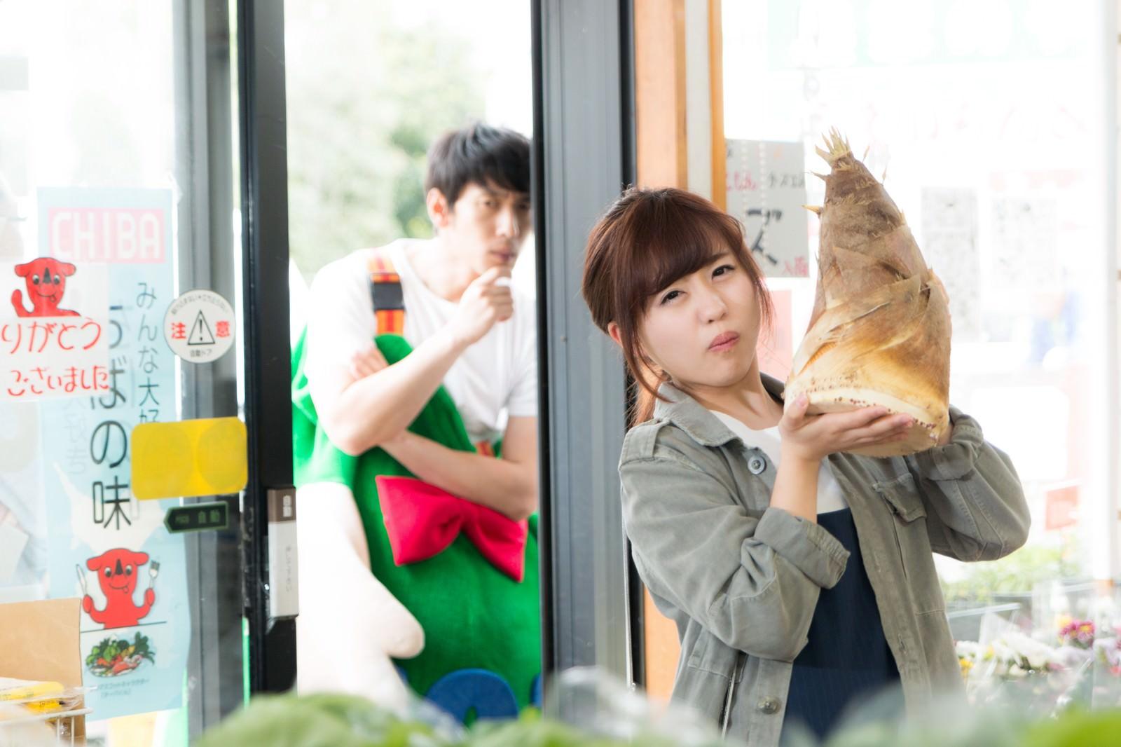 「商店で販売されていた大きなタケノコを物欲しげな顔で見つめる着ぐるみ姿のAD」の写真[モデル:大川竜弥 河村友歌]