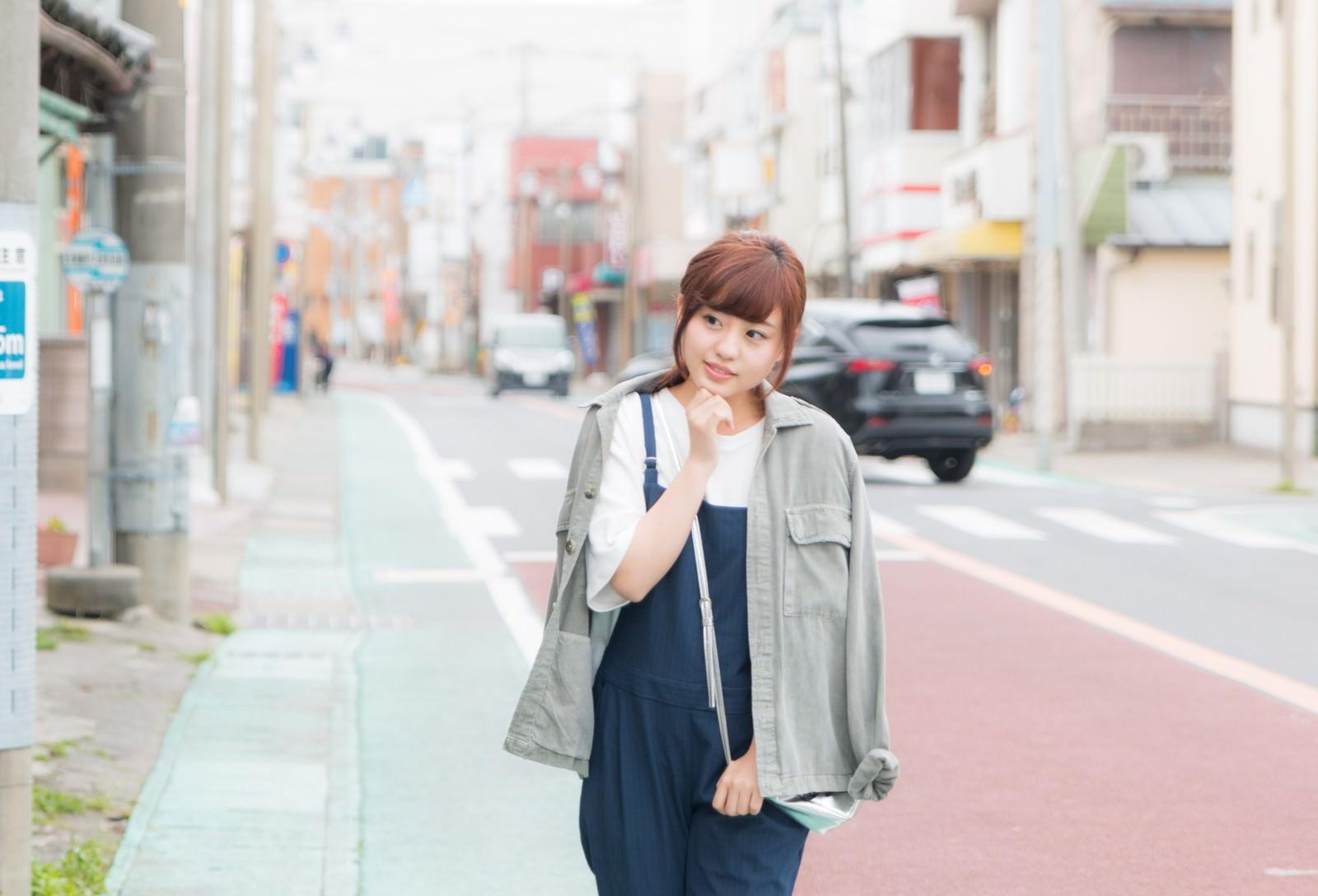 「商店街を歩きながら気になるお店を覗き込む女性観光客」の写真[モデル:河村友歌]