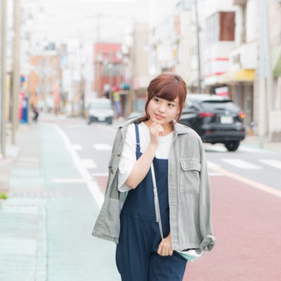 商店街を歩きながら気になるお店を覗き込む女性観光客の写真