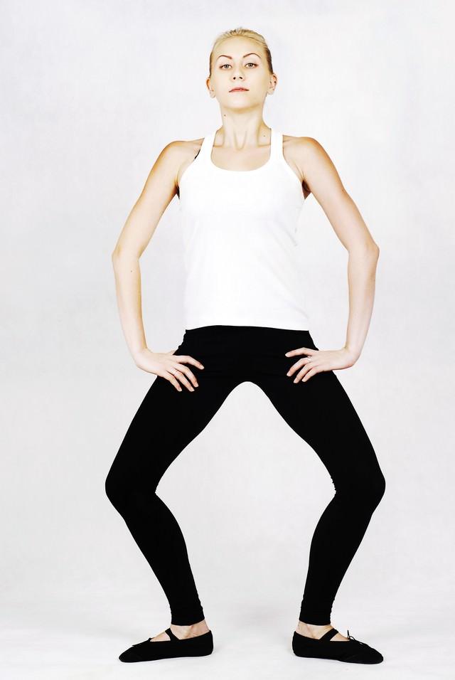 背筋を伸ばしたまま膝を曲げて柔軟体操する外国人の女性の写真