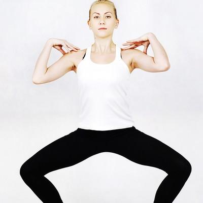 両肩に手を載せ腰を落とすストレッチをする外国人女性の写真