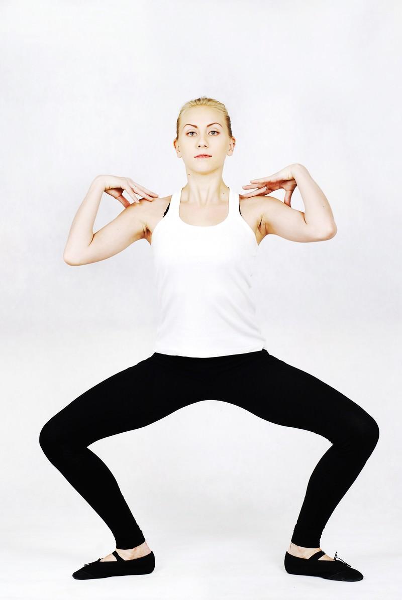 「両肩に手を載せ腰を落とすストレッチをする外国人女性」の写真[モデル:モデルファクトリー]