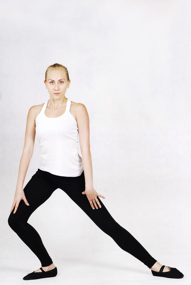 ゆっくりと片足に重心をかけていく外国人の女性インストラクターの写真