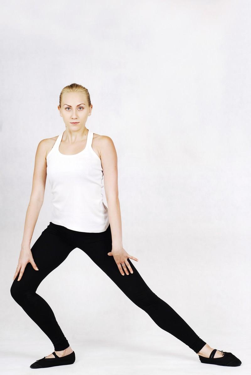 「ゆっくりと片足に重心をかけていく外国人の女性インストラクター」の写真[モデル:モデルファクトリー]