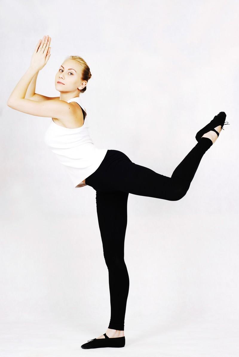 「合掌した手を離さないように片足を上げてバランスをとるロシア人のスポーツインストラクター」の写真[モデル:モデルファクトリー]