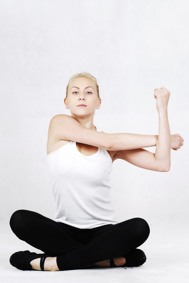 「あぐらの状態から背筋を伸ばすヨガ中の女性」の写真[モデル:モデルファクトリー]
