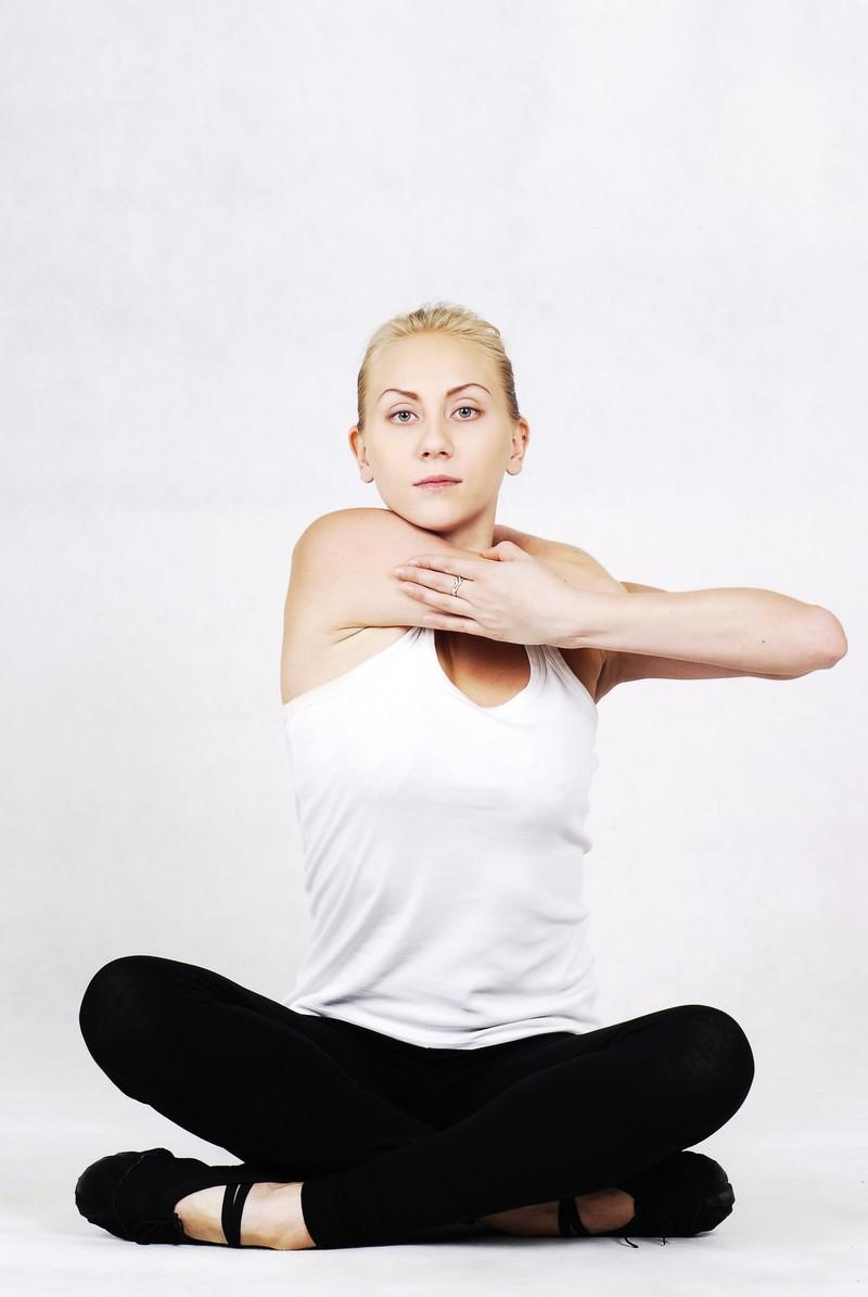 「あぐらの状態で首の後ろに手を回す外国人の女性インストラクター」の写真[モデル:モデルファクトリー]