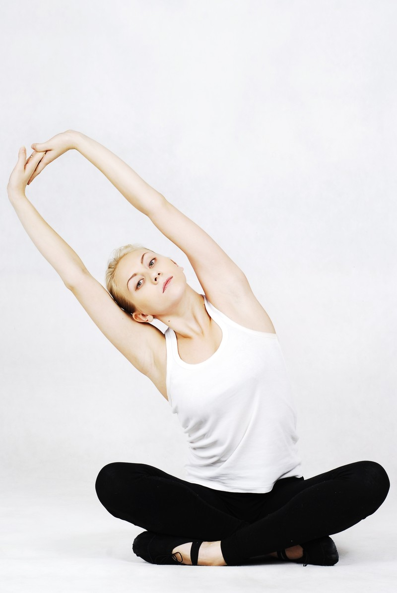 「あぐらの状態から両腕を伸ばす外国人の女性インストラクター」の写真[モデル:モデルファクトリー]