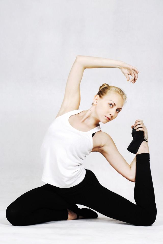足の裏を顔に引き寄せ上腕を強調する外国人の女性インストラクターの写真