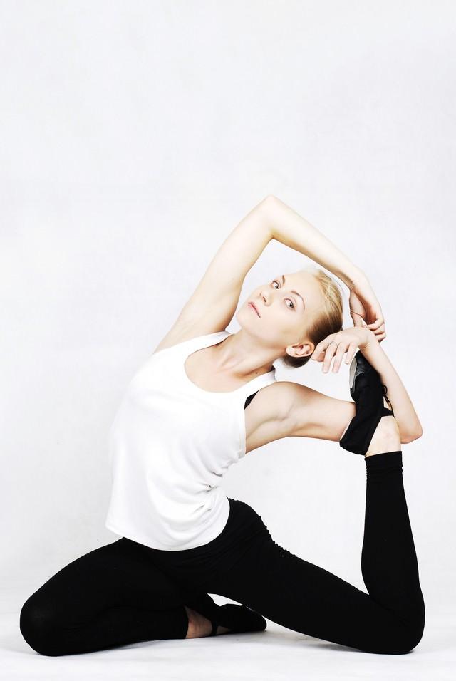 片足を引き上げながら柔軟をアピールする外国人の女性の写真