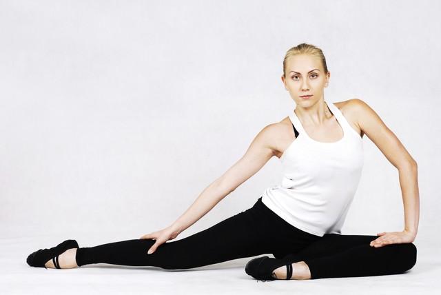 右足を入念に伸ばすバレエダンサーの写真
