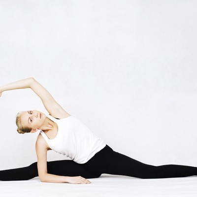 開脚しながら片腕を伸ばす体が柔らかいバレエダンサーの写真