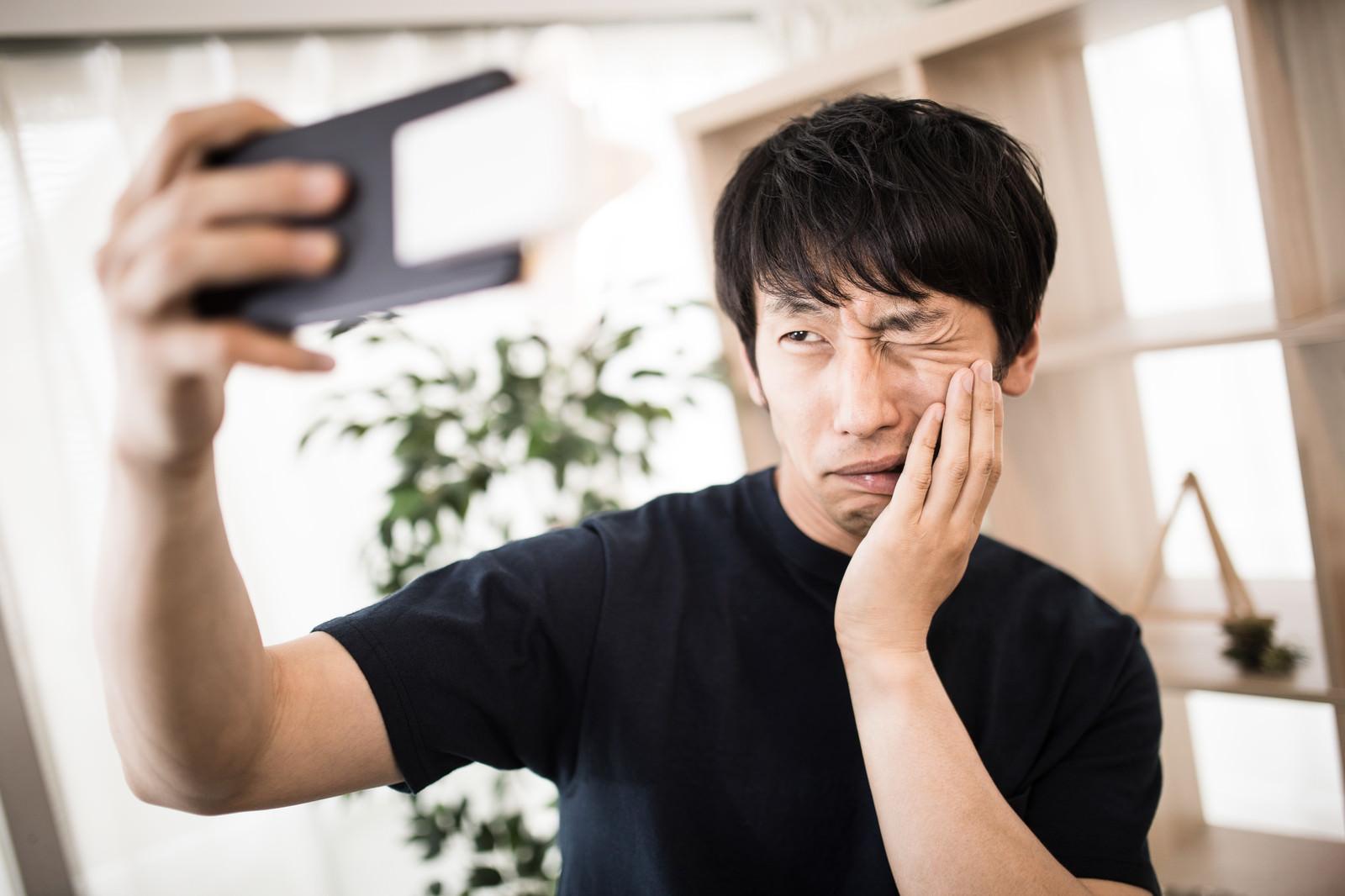 「虫歯痛ポーズ」の写真[モデル:大川竜弥]