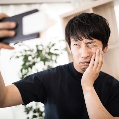 「虫歯痛ポーズ」の写真素材