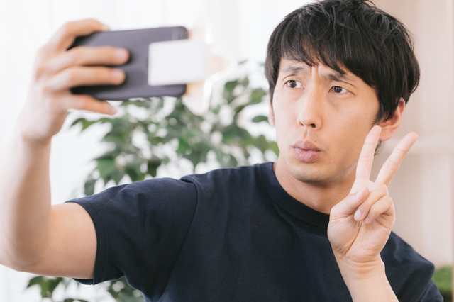 星型の自撮りライトを使っても表情が暗い男性の写真