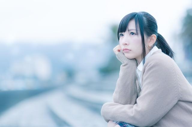 もの寂しげな表情で考えこむ女子高生の写真