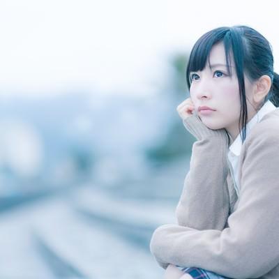 「もの寂しげな表情で考えこむ女子高生」の写真素材