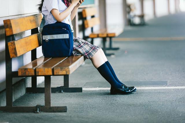 駅のホームのベンチに座るJKの写真