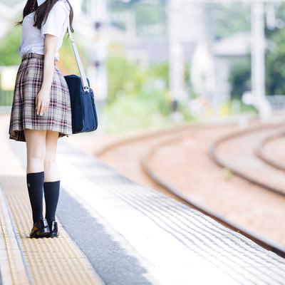 誰もいない駅のホームと振り返る女子高生の写真
