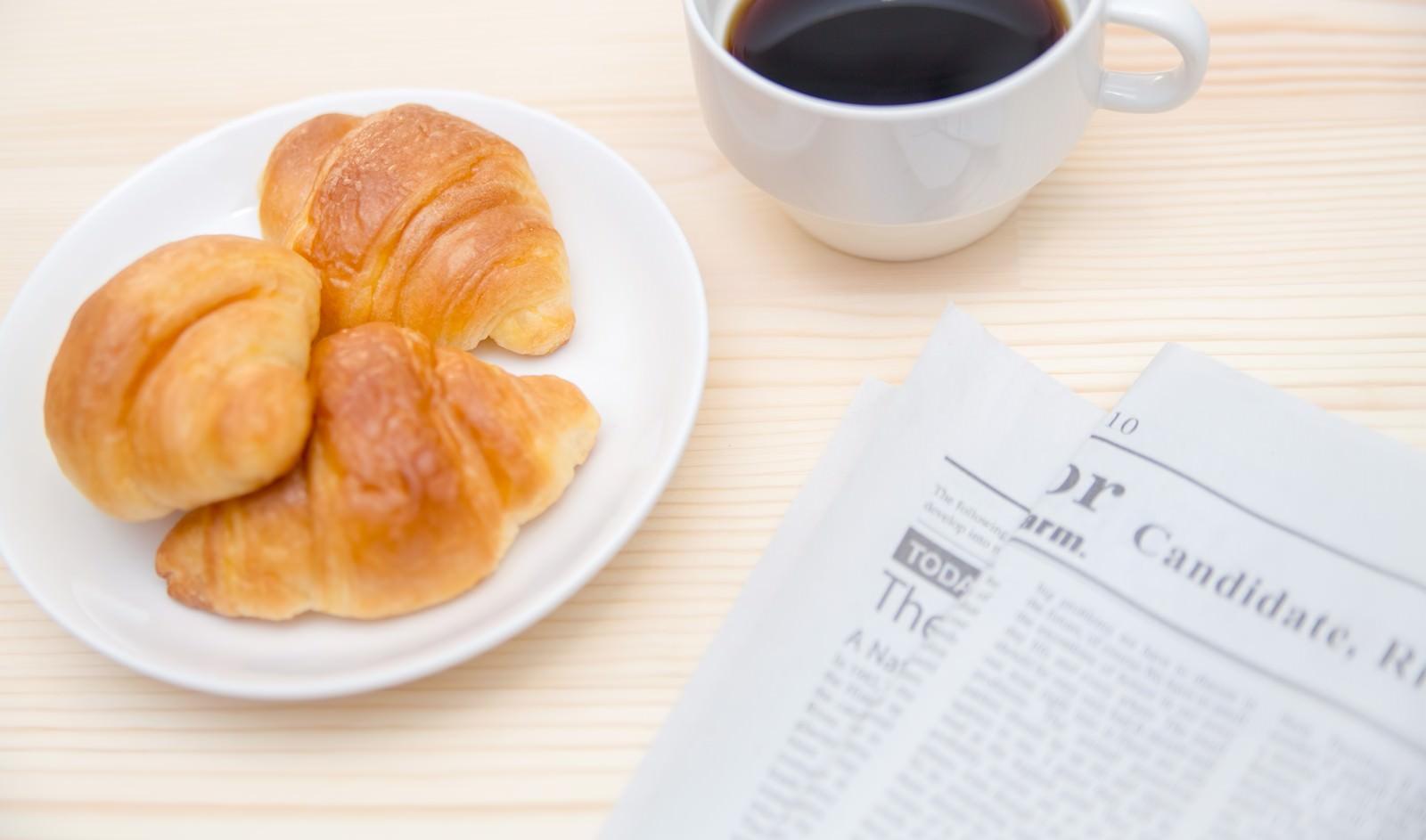 「クロワッサンとコーヒー、英文の新聞」の写真